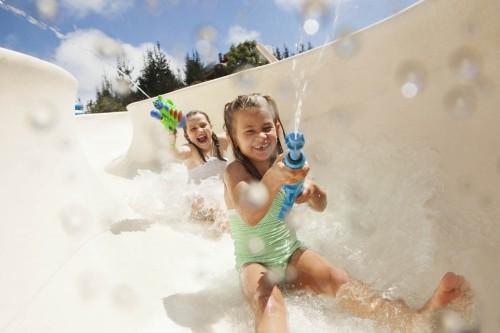 Girls (8-9), (10-12) going down water slide holding squirt guns