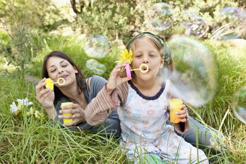 Mother and daughter (10-12) sitting in grass and blowing bubbles