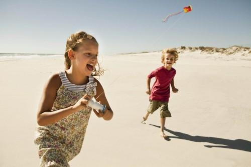 Boy  (6-7) and girl (8-9)  flying kite on sandy beach