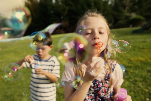 Girl (8-9) and boy (6-7)  blowing bubbles