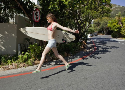 Surfer jumping on road