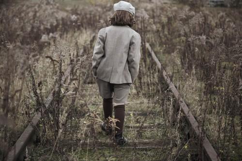 Boy walking on railroad tracks