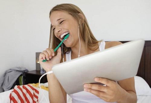 Young woman sitting on bed using tablet pc and brushing teeth